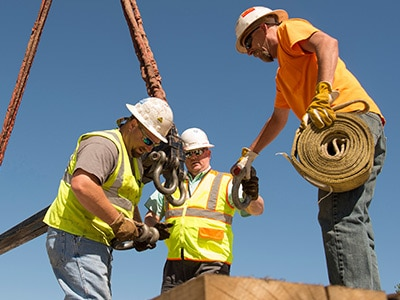 Three men with crane hook on construction site