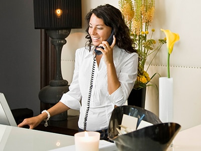 woman on phone and at computer at hotel check in desk