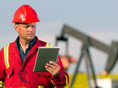 Man with clipboard in front of oil pump